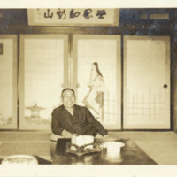 A smiling Japanese man sitting at a table in Japanese…