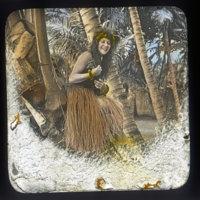 Woman wearing a grass skirt holding a ukulele