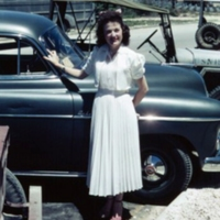 [Woman standing in front of car, jeep, bus]