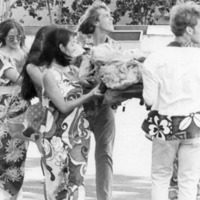 Seven young people dressed in aloha wear carrying…