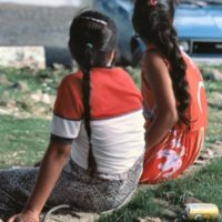 Backs of Two Girls Sitting on Stone Wall