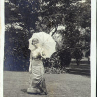 Woman Holding an Umbrella Standing in Front of a Tree