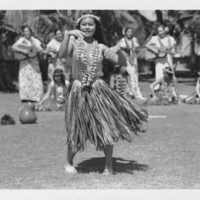 Woman in ti-leaf skirt performing hula with musicians