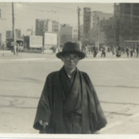 A bespectacled Japanese man standing in the street…