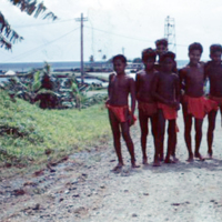 [Six young boys standing on a road]