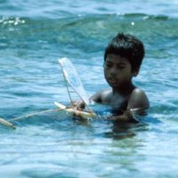 Boy Playing with Toy Canoe