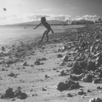 Child throwing rock on rocky shore