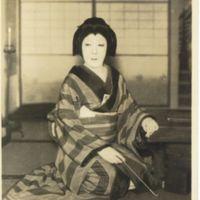 Kaizawa 1-122: Kabuki actor as a woman sitting with a…