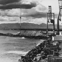 Cranes and shipping containers along breakwater