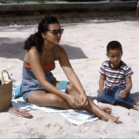 Lady and a little boy lounging on a beach