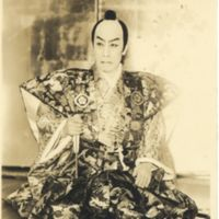 Kaizawa 1-042: Kabuki actor sitting with a folding fan…